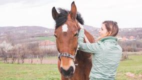 大农场的美丽的少妇有一匹棕色马的 免版税库存图片