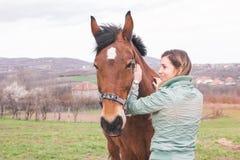 大农场的美丽的少妇有一匹棕色马的 库存照片