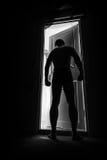 大力士在晚上站立近的门 免版税库存图片