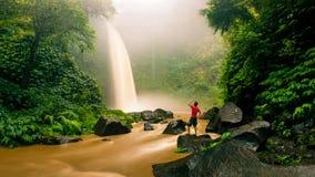 年轻大力士旅客享受壮观的早晨视图,美丽的Nungnung瀑布 免版税库存照片