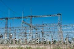 大功率电杆在市区 能量电传输,高压供应 查出的拉长的现有量排行次幂白色 库存照片