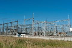 大功率电杆在市区 能量电传输,高压供应 查出的拉长的现有量排行次幂白色 免版税库存照片