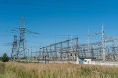 大功率电杆在市区 能量电传输,高压供应 查出的拉长的现有量排行次幂白色 免版税库存图片