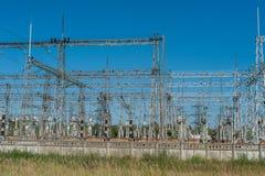 大功率电杆在市区 能量电传输,高压供应 查出的拉长的现有量排行次幂白色 免版税图库摄影