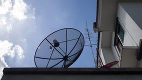 大卫星盘,小红色卫星盘和天线电视在房子屋顶反对有蓝天的和白色云彩 免版税库存图片