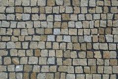 大卵石向铺背景的街道扔石头 免版税库存照片