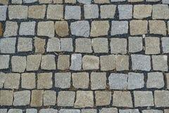 大卵石向铺背景的街道扔石头 库存图片