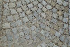 大卵石向铺被环绕的背景的街道扔石头 免版税库存图片