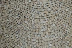 大卵石向铺被环绕的背景的街道扔石头 库存图片