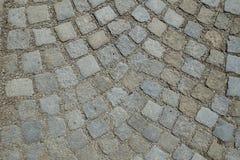 大卵石向铺被环绕的背景的街道扔石头 免版税图库摄影