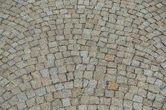 大卵石向铺被环绕的背景的街道扔石头 免版税库存照片