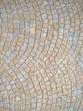 大卵石向铺被环绕的背景的街道扔石头 库存照片