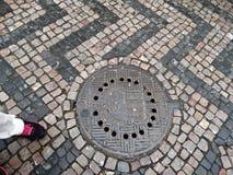 大卵石石街道和人孔盖 图库摄影