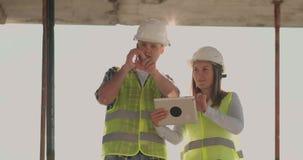 大厦在有女性的建筑和男性工程师使用形象化的片剂和的手机大厦 股票视频