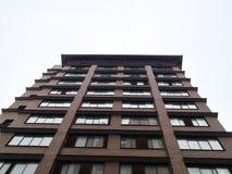 大厦在离开在高度秋天多云天气的一个锐角 免版税库存照片