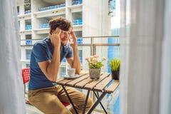 大厦工作懊恼的阳台的年轻人外面 噪声概念 从大厦尘土的空气污染 免版税图库摄影