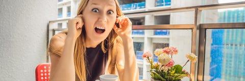 大厦工作懊恼的阳台的年轻女人外面 噪声概念 从大厦尘土横幅的空气污染 库存图片