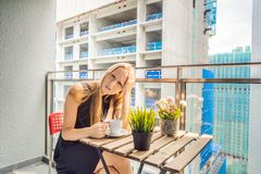 大厦工作懊恼的阳台的年轻女人外面 噪声概念 从大厦尘土的空气污染 免版税库存照片