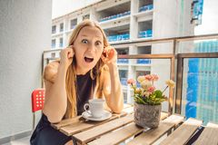 大厦工作懊恼的阳台的年轻女人外面 噪声概念 从大厦尘土的空气污染 库存照片