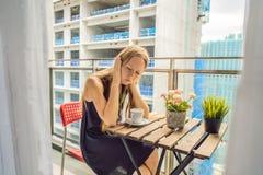 大厦工作懊恼的阳台的年轻女人外面 噪声概念 从大厦尘土的空气污染 库存图片