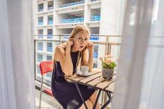 大厦工作懊恼的阳台的年轻女人外面 噪声概念 从大厦尘土的空气污染 免版税图库摄影