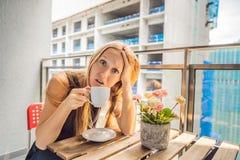 大厦工作懊恼的阳台的年轻女人外面 噪声概念 从大厦尘土的空气污染 图库摄影