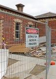 大厦有标志、护拦和瓦砾的爆破位置 免版税图库摄影