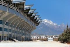 大厦有美丽的山的城市体育场在背景中 库存图片