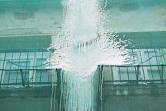 大厦的恢复和一个防护绿色大厦用慢慢流掉屋顶的冻水捕捉 免版税库存照片