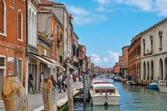 大厦看法,在运河前面,有人和小船的在Murano 免版税库存照片