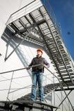 大厦站立在金属楼梯的控制审查员 免版税库存照片