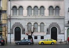 大厦街市与汽车沿走的街道和的妇女停放了-雅典希腊01 04 2018年 免版税图库摄影