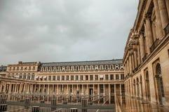 大厦门面和内在庭院有人的在雨天在皇家宫殿在巴黎 图库摄影