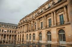 大厦门面和内在庭院有人的在雨天在皇家宫殿在巴黎 免版税库存照片