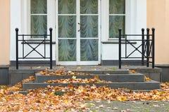 大厦门廊,散布与下落的秋叶 免版税库存图片