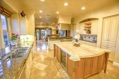 大厨房在有大花岗岩柜台的样房打开概念 免版税库存图片