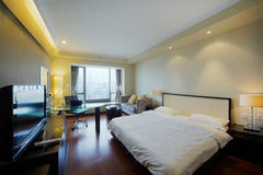 大双人床在时髦的轻的空间 免版税图库摄影