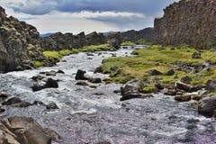 大反差风景由在黑暗的小山之间的山小河制成在Thingvellir国家公园 免版税库存图片