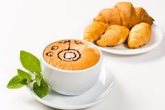 大咖啡和新月形面包在板材 库存照片
