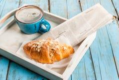 大咖啡杯、新月形面包和报纸 库存图片