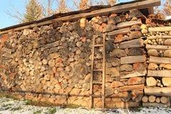 大土墩干燥堆与屋顶的木柴在一个庭院里在冬天 免版税库存照片