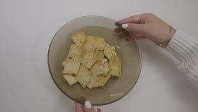 大土豆片碗 吃芯片,特写镜头的妇女的手 妇女` s手扭转芯片板材  库存图片