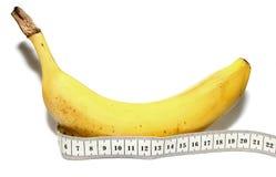 大在白色背景隔绝的香蕉和测量的磁带,例如人的大阴茎 免版税图库摄影