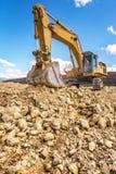 大在路的建筑工作的挖掘机运动的地球 免版税图库摄影