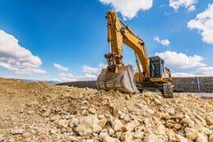 大在路的建筑工作的挖掘机运动的地球 免版税库存图片