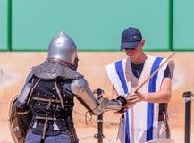大地主在戈伦公园帮助一个骑士佩带装甲在一个骑士节日在以色列 免版税库存照片