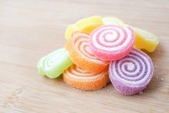 大块五颜六色的胶粘的果冻糖果滚动用糖,投入了木头 免版税库存照片