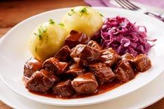 大块的炖牛肉用在土豆旁边的美味调味汁 免版税库存图片
