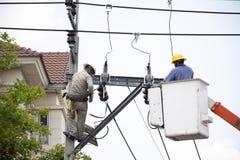 大城市在电柱子或电线杆的电当局运作的修理电气系统的电工工作者 库存图片