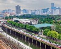 大城市街道,装载用汽车,沿路河公园有绿色树的,都市建筑学的交通堵塞 库存照片